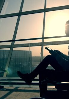 Businessman-using-tablet-computer-at-the-airport-silhouette-of-a-man-traveler-with-backpack